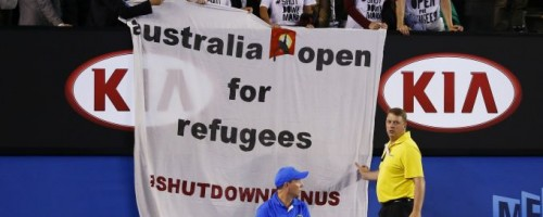A line judge and security officer react as protesters display a banner during the men's singles final match between Djokovic of Serbia and Murray of Britain at the Australian Open 2015 tennis tournament in Melbourne